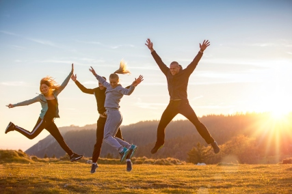 Group of friends running happily together in the grass and jumping